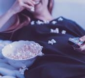 Lifeside woman wearing black dress shirt eating popcorn 1040159